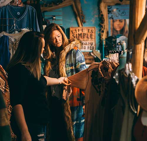 two women looking at western wear clothes