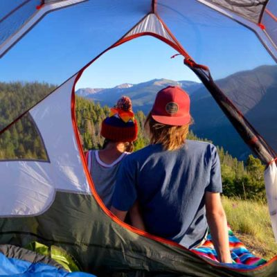 couple enjoying the mountain view from their tent